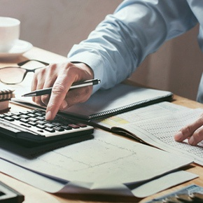 man using a calculator for cross-border payments